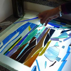 A customer creates a beautiful picture from pieces of glass before glueing them to the backing glass and then grouting the finished design