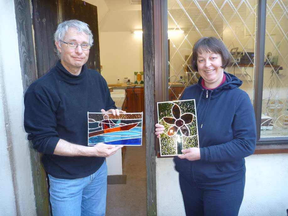 Two happy students show off their copper foiled stained glass panels made on a two day stained glass course in Kent