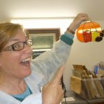 A student happily shows off the glass suncatcher that she's just finished making