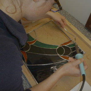 Copper foiled stained glass student solders her first stained glass window panel
