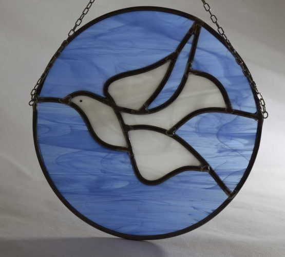 A circular traditional stained glass leaded light of a dove in flight. Learn to make a stained glass panel on our course!
