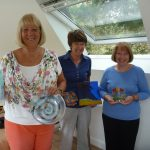 Glass fusing class proudly show off what they've made
