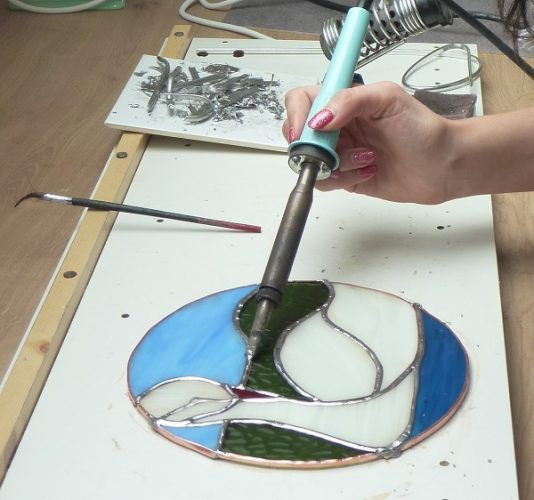 photo of copper foiled swan panel being soldered on a two day stained glass course in Kent