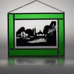 stained glass picture of historic Chilham in a leafy green glass surround