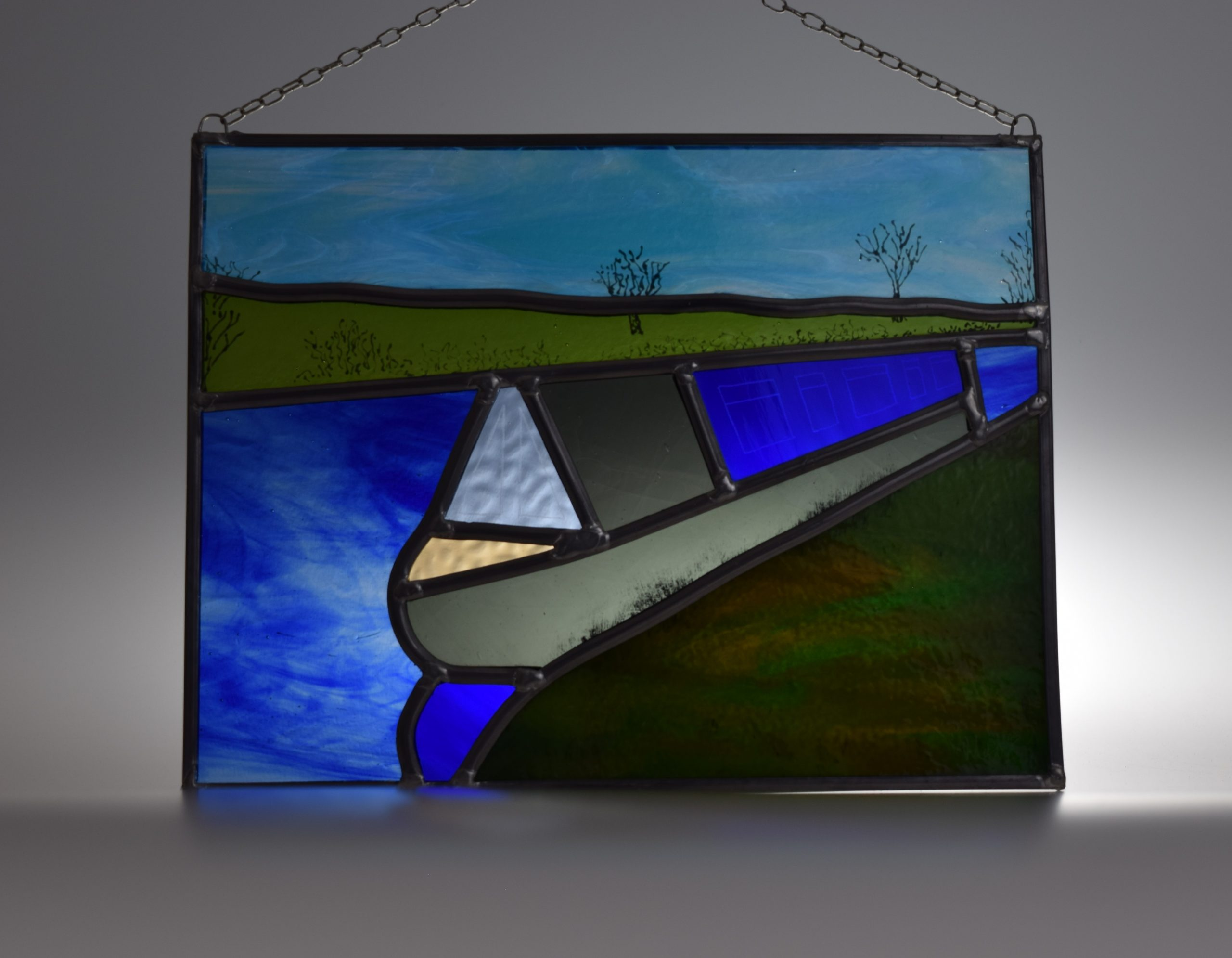 Stained glass panel of a narrowboat moored in the countryside