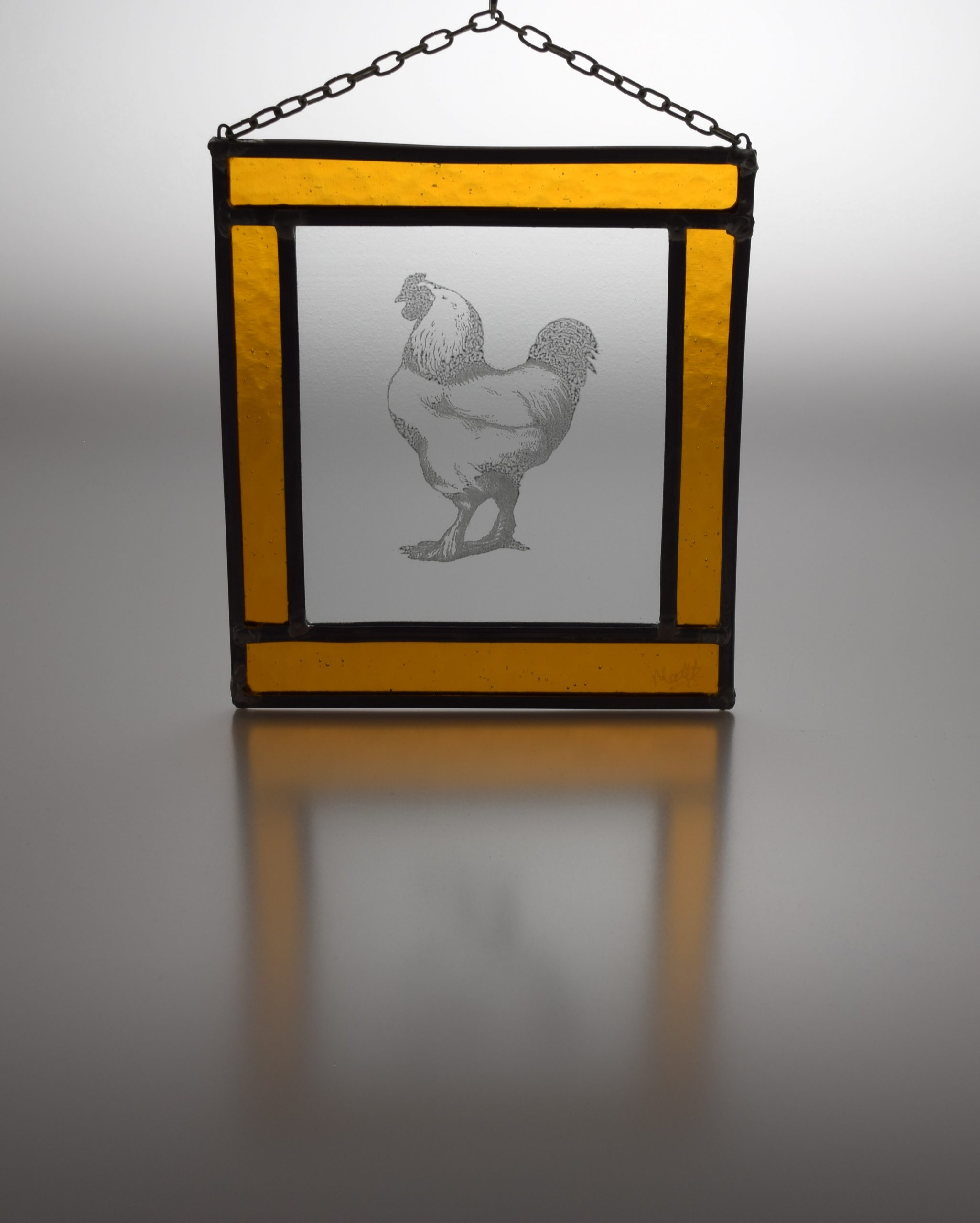 Stained glass cock picture with amber yellow glass frame and lead surround, with hanging chain attached