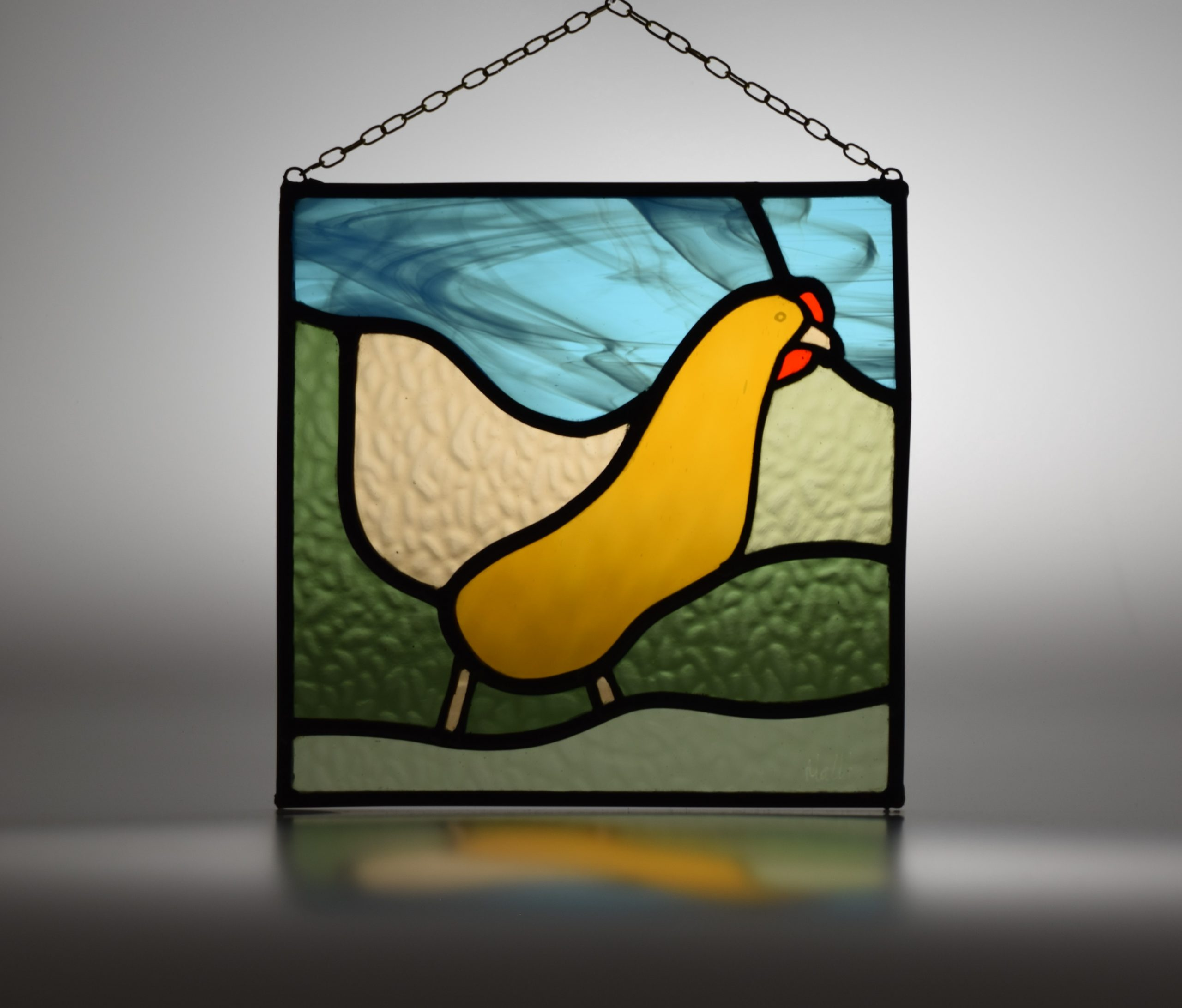 Stained glass picture of a chicken, with hanging chain attached