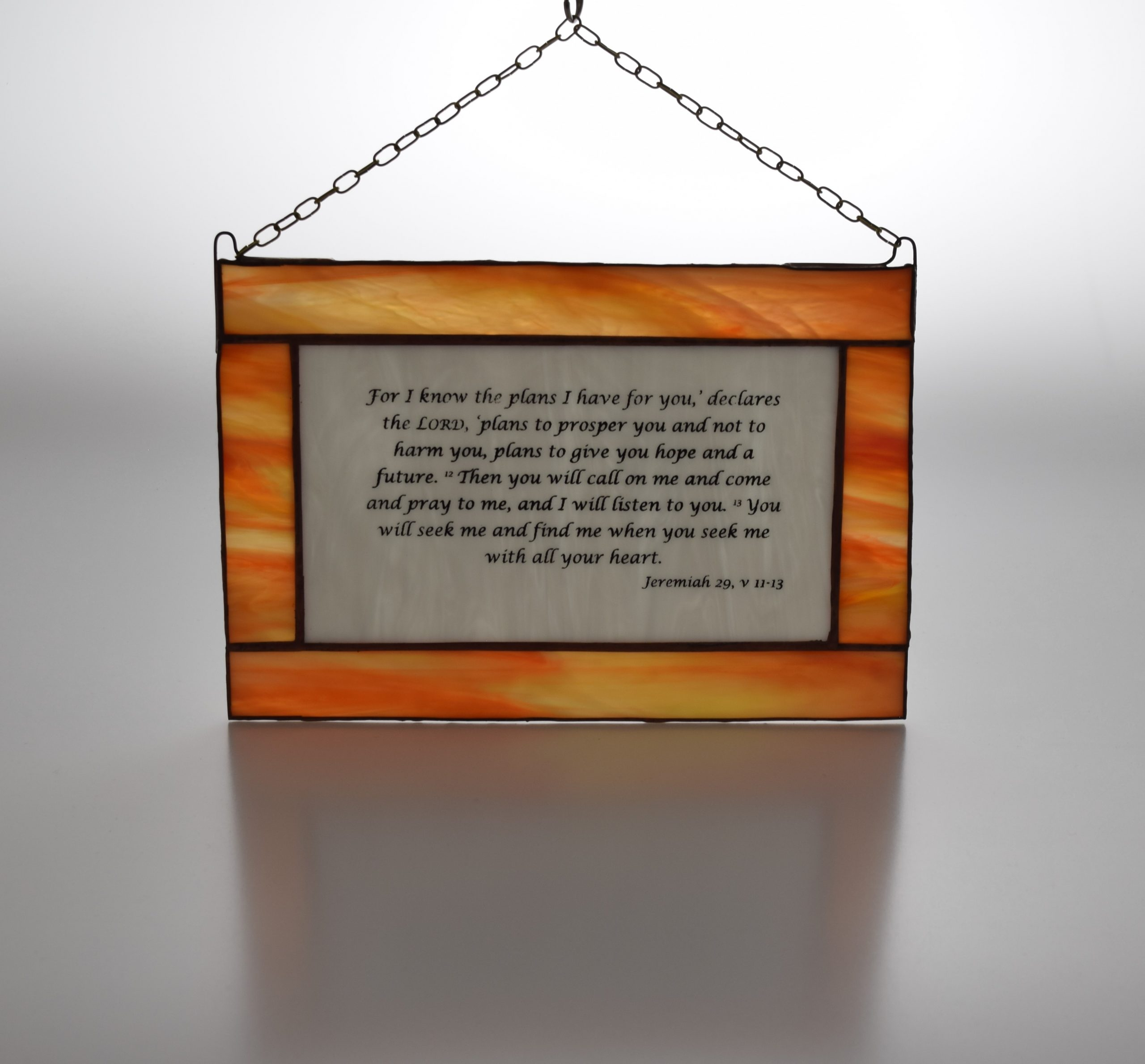 An attractive stained glass panel bearing the words from Jeremiah 29, verses 11 - 13 on white glass, with a glass border in shades of orange and a hanging chain.
