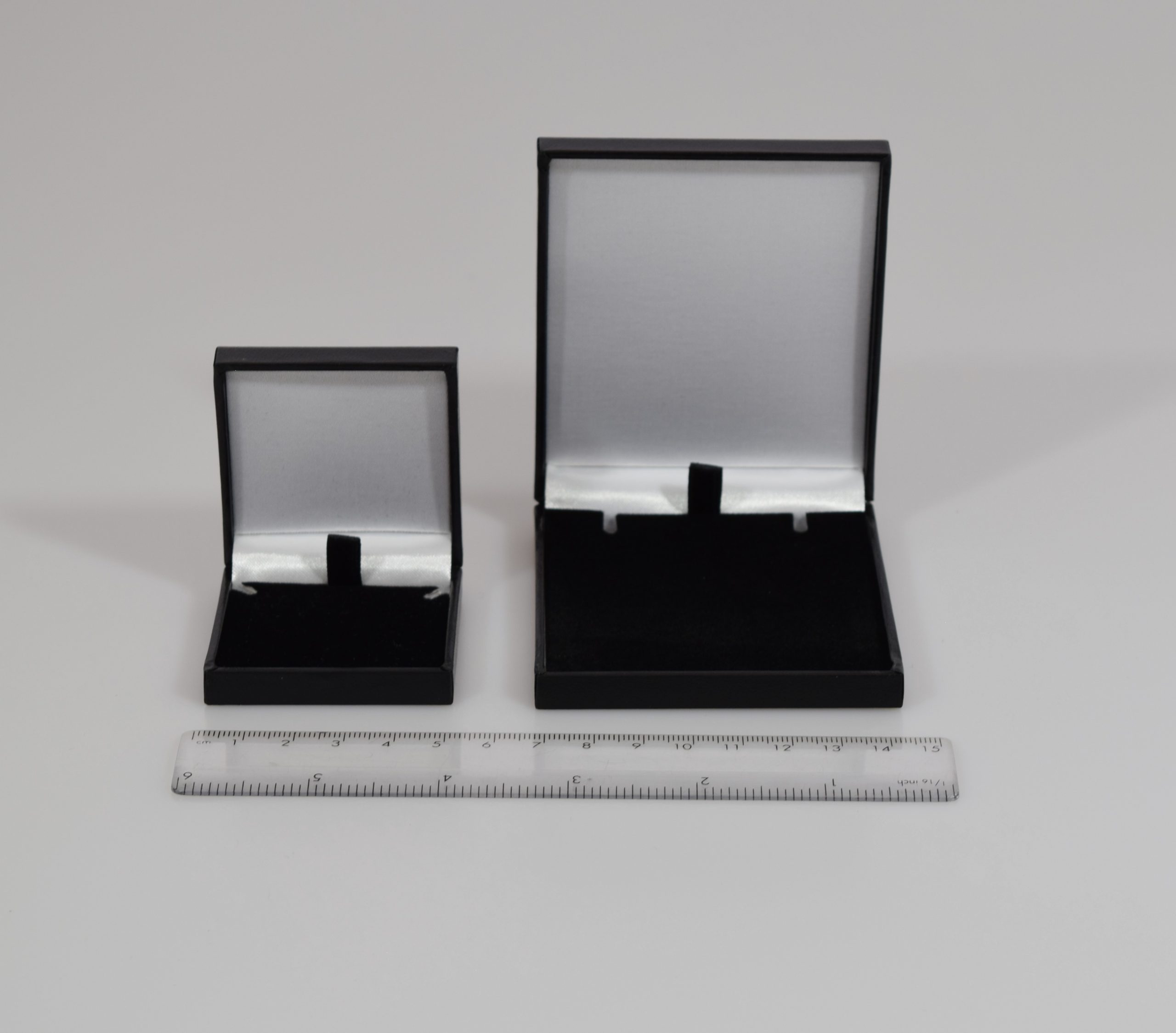 Hinged jewellery boxes that fit Royal Mail large letter classification. Black leather-effect finish on the outside and white satin inside the lid, with black velour pad inside.