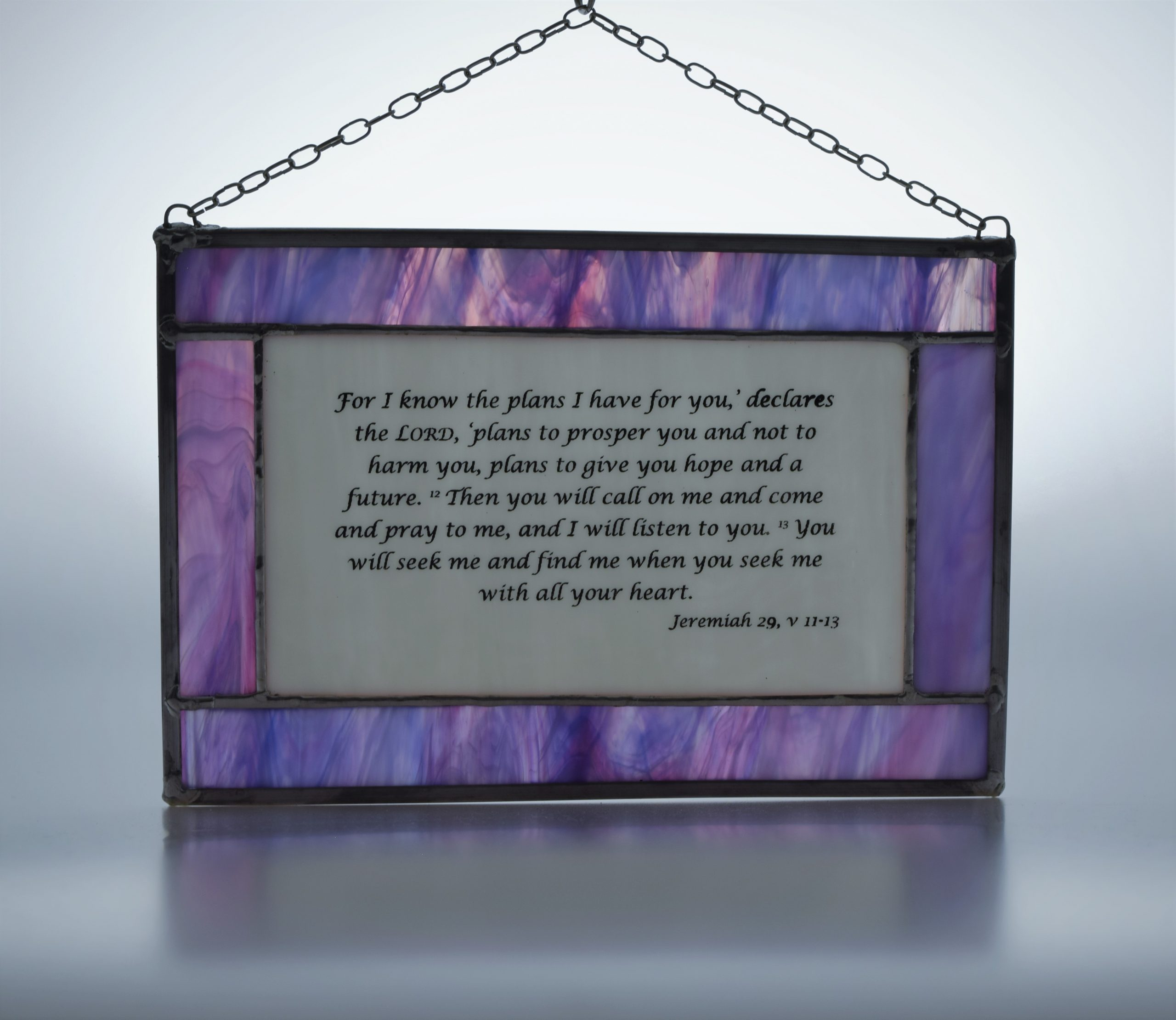 Stained glass panel in lilac and white, with old testament text from the book of Jeremiah