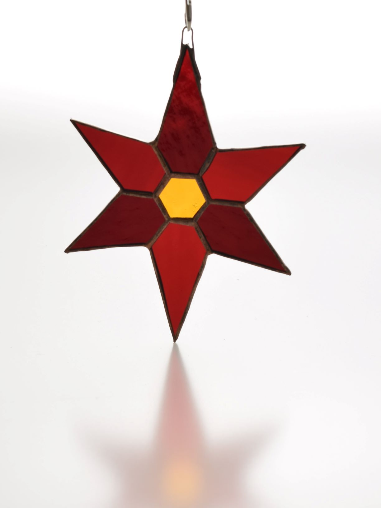Stained glass six pointed star in two shades of red glass with gold glass hexagon in the centre