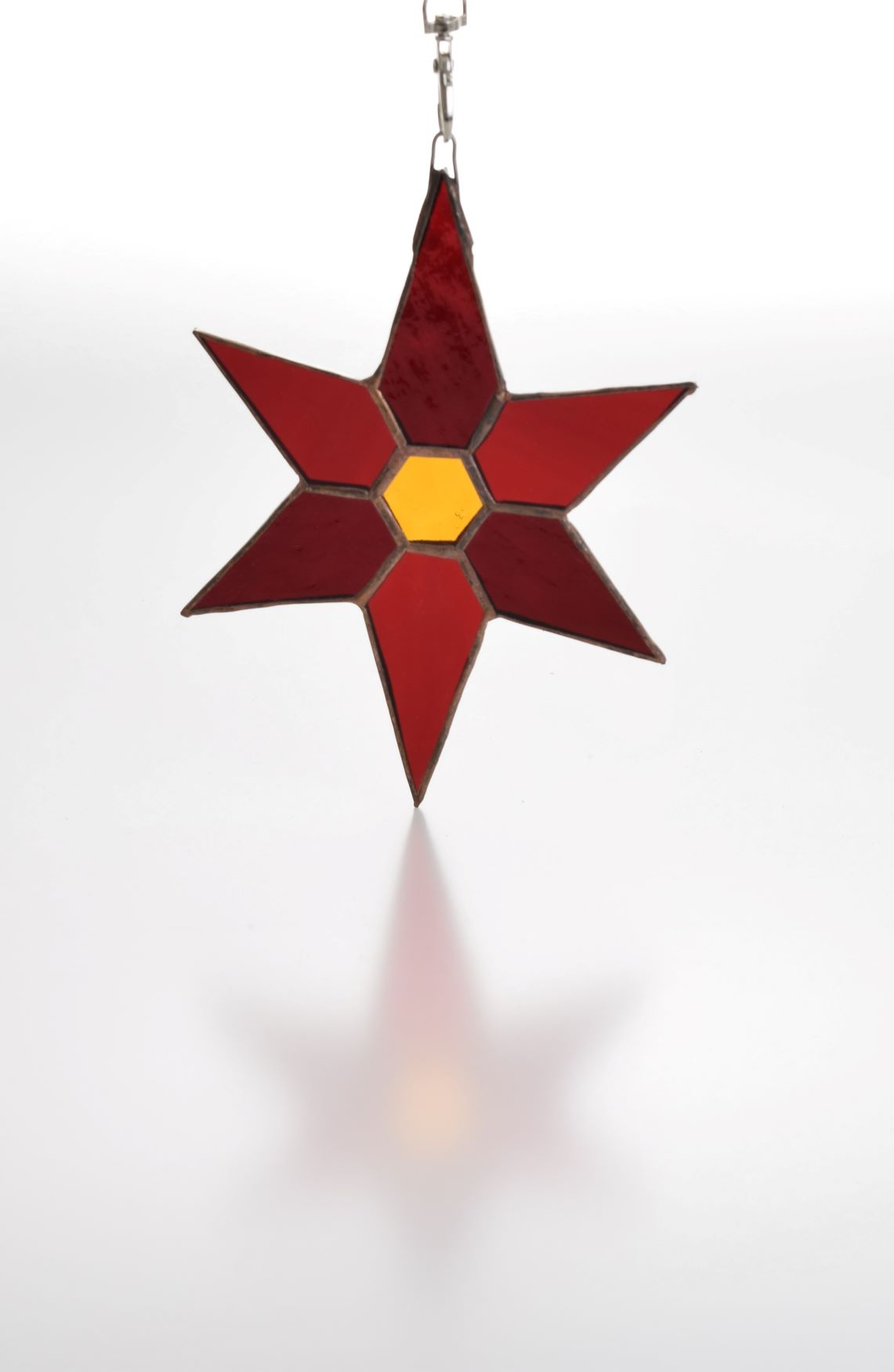 Copper foiled stained glass star in two shades of red glass with a hexagonal gold glass centre