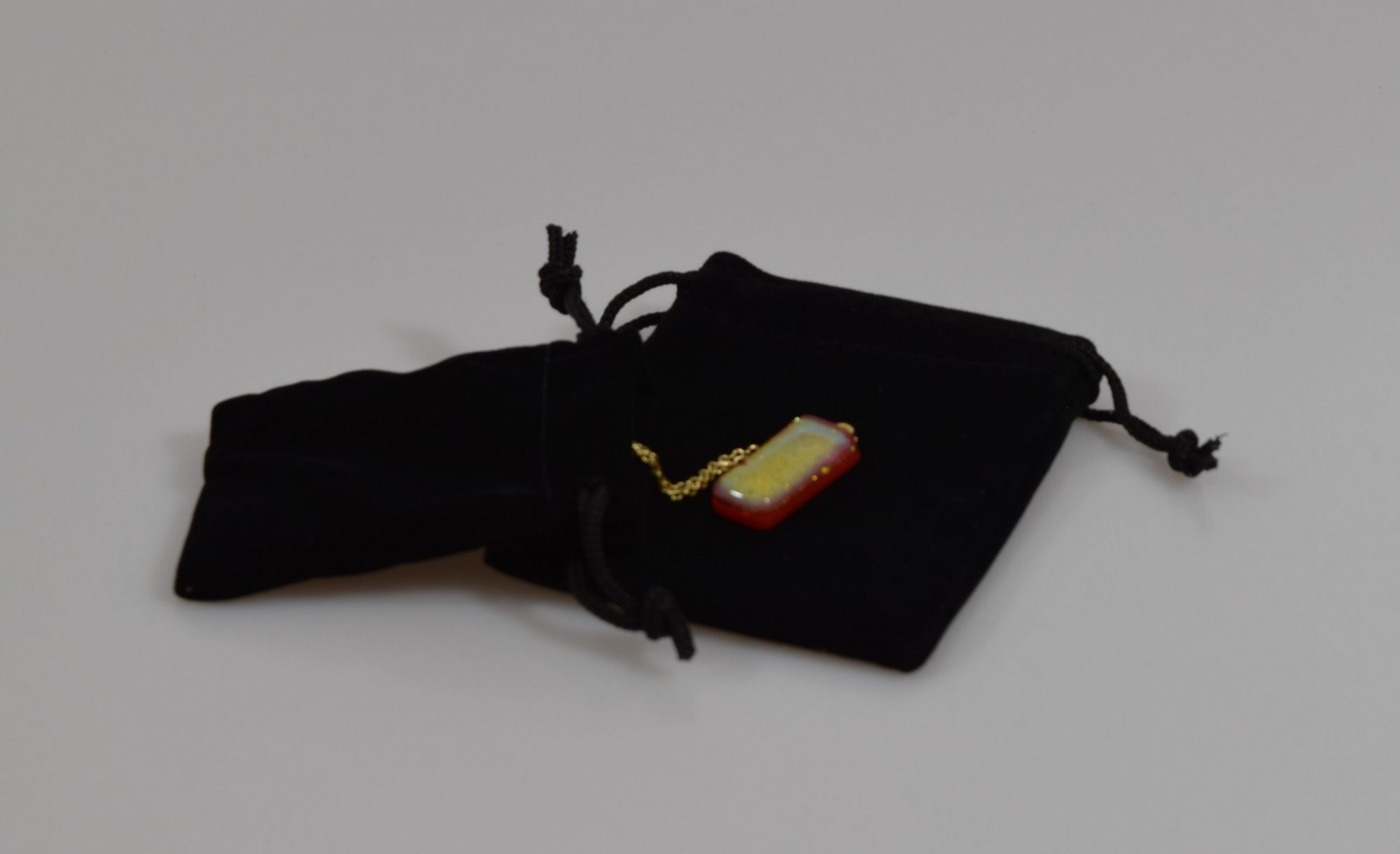 black drawstring bags in soft velour fabric. Jewellery available to buy separately.