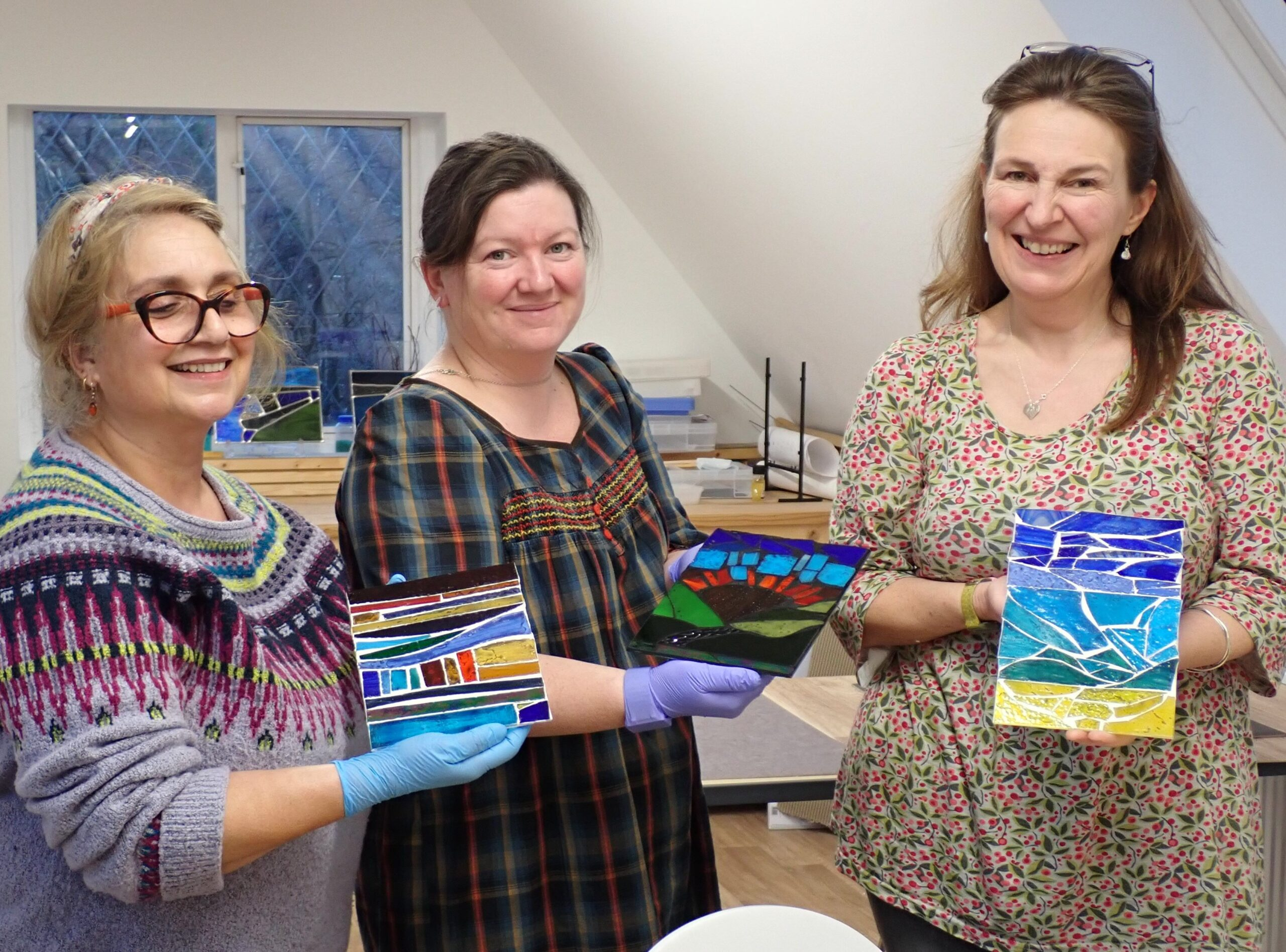 Three customers show off the stained glass mosaic pictures that they've made on a one day course in our Chilham workshop