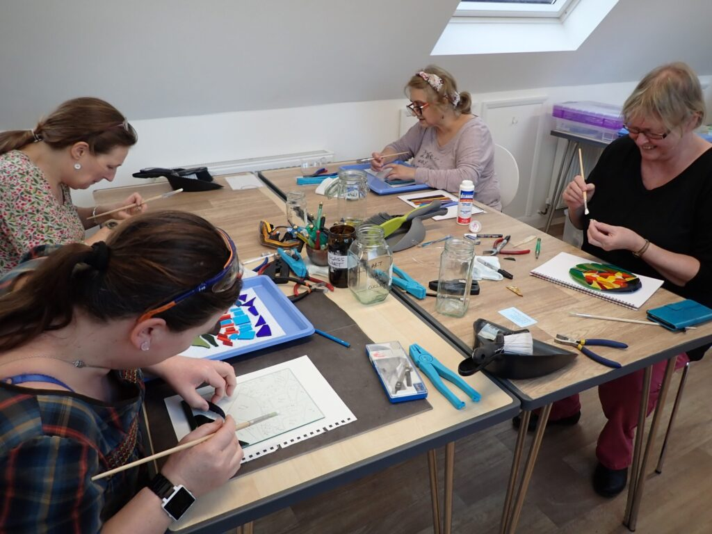 Four visitors to Creative Retreats and Holidays' glass studio glue their stained glass mosaics before finishing them with grout