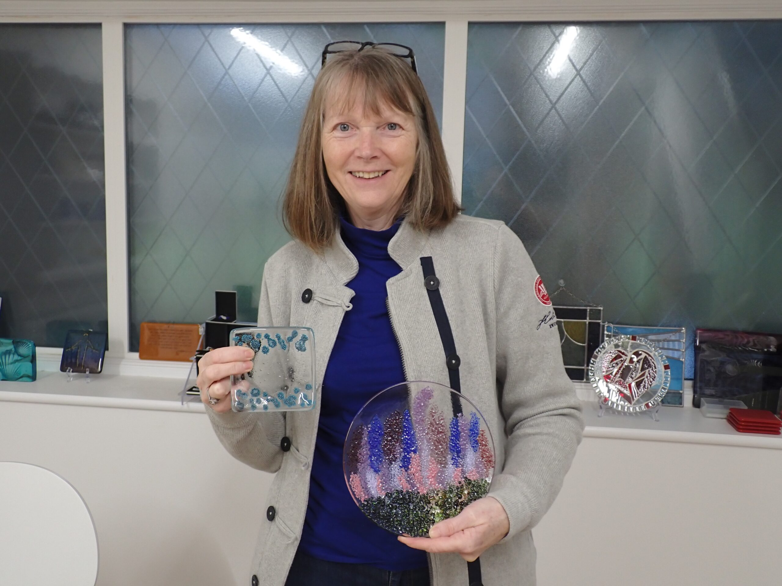 A delighted student collects her creations which she made on a glass fusing taster day with Creative Retreats and Holidays - a plate decorated with delphiniums and a spotty glass dish